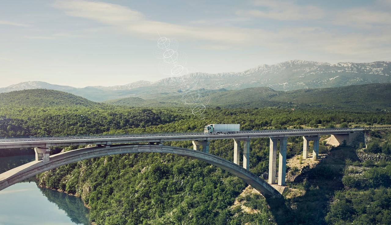 Ένα συνδεδεμένο φορτηγό Volvo περά από μια γέφυρα σε μια απομονωμένη τοποθεσία
